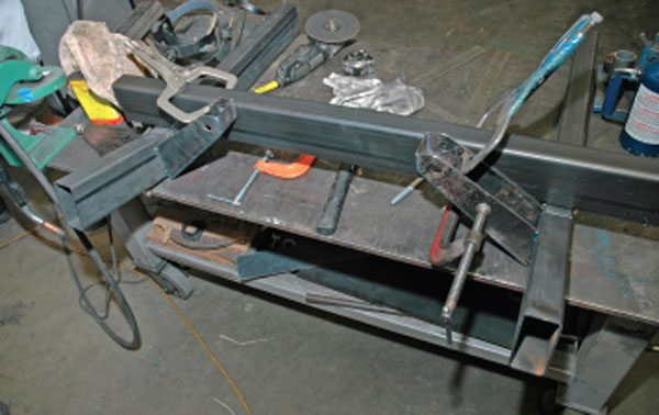 Both frame rails are tacked to the welding table and the suspension pickup points are tacked into place. From this supported framework, we'll create the crossmember and add other necessary fittings.