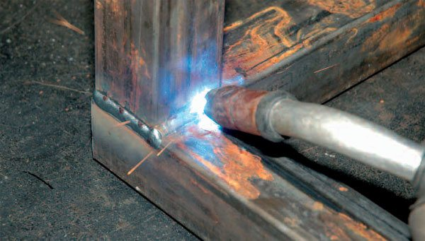 Notice how the MIG gun is angled toward the arc point as Russ pushes a weld along a joint.