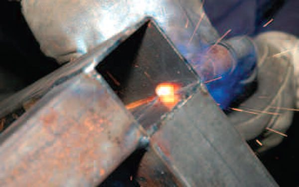 Tack the top of the table into place and then remeasure with the squares and a spirit level before you run a bead on any piece. In this photo you can see the glow of the weld through the back side of the box steel. This shows us that the weld is making good penetration through the material.