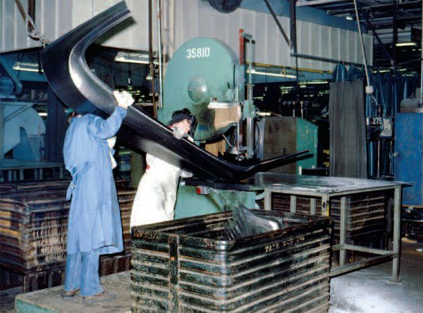 After a panel is stamped, it may still need detail work. Employees in this 1975 GM plant are shown performing some of that work. (Photo supplied by General Motors Corp.)