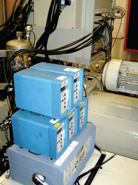 The blue boxes in the foreground are signal processors for in-cylinder pressure measurements. The business end of a million-dollar production-level engine dyno can be seen in the background.