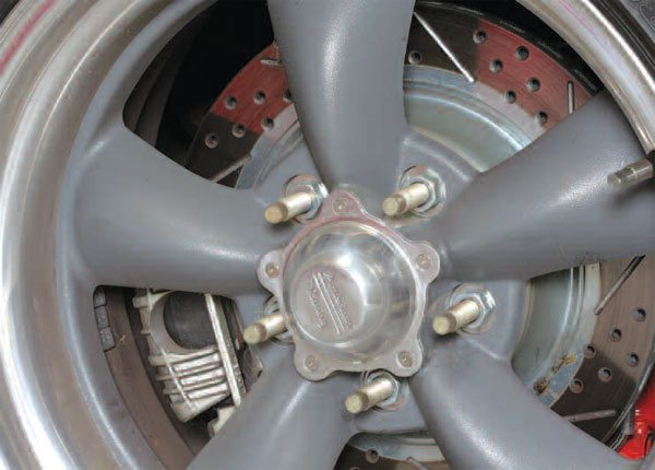 Many use this typical aftermarket stud and nut combination, but the NHRA rules do not require this much stud past the end of the lug nuts. Notice the rear disc brake conversion with drilled and slotted rotors.