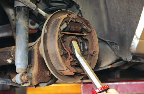 Use a large pry bar or even an old axle shaft to remove the axle shaft wheel end. Chances are pretty good that your wheel end and brakes are rusty and dusty like the axle, so you may need to replace some of this hardware.  (Randall Shafer)
