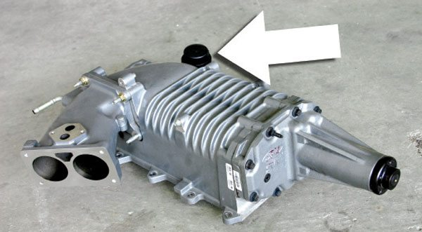 This Eaton Model 112 compressor from a 2003 Cobra is another variant of the positive displacement compressor. The throttle body and IAC motor are installed upstream of the compressor inlet. A bypass valve (arrow) is also integrated with the back side of the unit. (Nate Tovey)