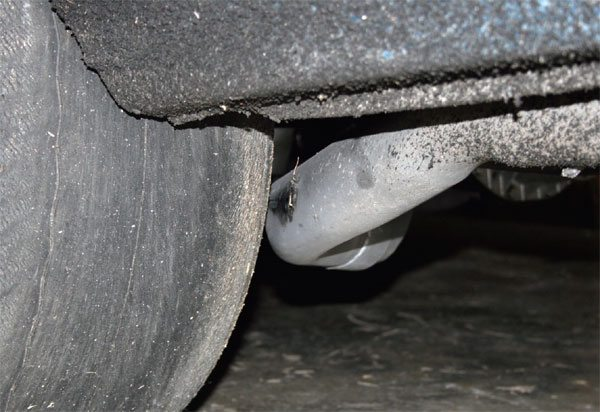 Even if your tires clear everything while sitting still, the car's body will roll going around corners and create an issue. This tire is hitting the tail pipes but it is minimal, and if a different offset wheel would not work I would let it happen as opposed to using a narrower tire.