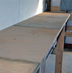 When the top shelf has been made of 2 x 6 lumber, put a sheet of 1/2-inch plywood on top. It provides a smooth surface and ties all the lumber together.
