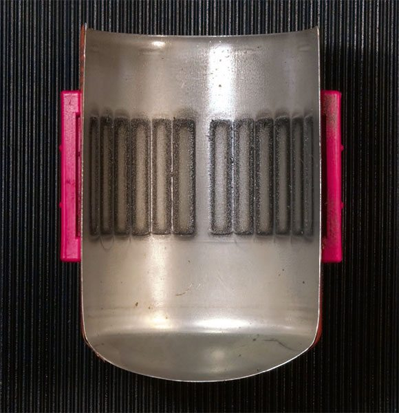 A Filtermag attracts all metal particles that pass through the filter housing. As shown here the captured material aligns itself according to the mag¬netic field created by attaching the Filtermag to the outside of the filter canister.