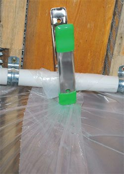 Use inexpensive spring clips from the home supply store to attach the plastic sheeting to the PVC pipes near the ceiling and on the vertical posts of your coating booth.