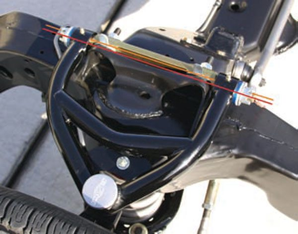 These tubular upper A-arms are equipped with offset cross shafts. The red line shows the centerline of the bushings in the A-arms. The orange line shows the centerline of the cross shaft where it mounts to the frame bracket. The offset is about 3/8 inch, or the equivalent of three 1/8-inch alignment shims. In this photo, the cross shaft is being used to provide more positive camber because the suspension is unloaded. Once the car is assembled and the final alignment is set, it may be reversed to provide more negative camber. (Photo Courtesy Magnum Force Racing)