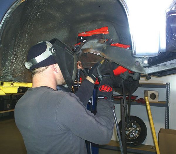 Be aware that getting a high level of performance out of an air-spring-equipped car takes some work and dedication. This fabricator is cutting the original spring pocket open with a plasma cutter to make room for the much-larger-diameter Shockwave. (Photo Courtesy RideTech)