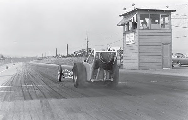 This shot provides an excellent view of the racing surface, as a dragster begins to haze the tires off the line. The tower is in clear view, and you can also see the spectators lined up atop the banked sidelines of the drag strip. (Photo by T. O'Shea, Courtesy www.doverdragstrip.com)