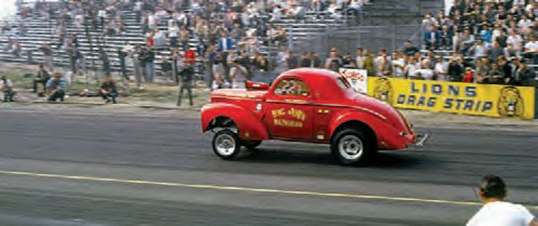 "From the other side of the track, you can see the steepness of the spectator seating. ""Big John"" Mazmanian rips off the line in his well-known supercharged gas Willys coupe, which perfectly embodies the gasser styling we all know and love. (Photo Courtesy Don Gillespie Collection)"