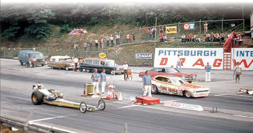"""As time went on, the track grew in popularity and changed with the times. The retaining wall on the left side of the track wore huge """"Pittsburgh International Dragway"""" signage, which always stood out in photos like this early 1970s matchup, featuring an injected Hemi dragster and The Fokky Farmer, a Pinto funny car. (Photo Courtesy Bill Truby)"""