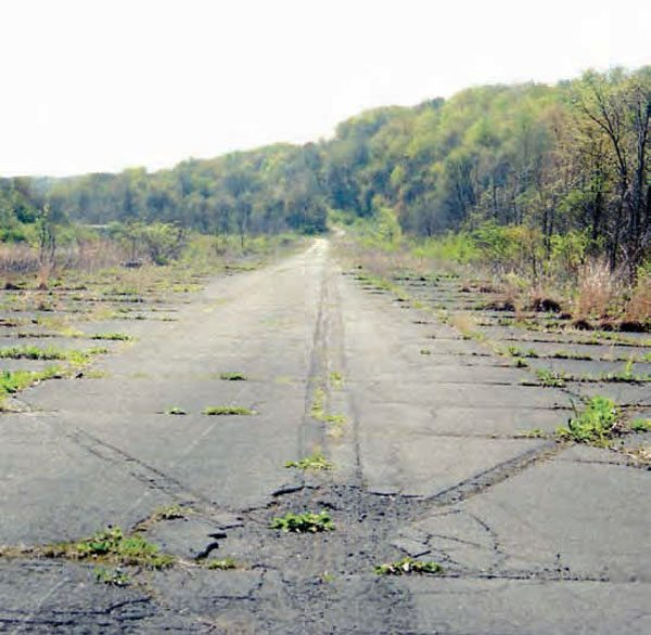A narrow strip of the pavement has resisted the overgrowth of weeds and trees, but the property has the potential to be cleaned up in order to preserve the old pavement. PID reunion events are currently held at Pittsburgh Raceway Park, which was once a competing track in the area. (Photo Courtesy Bill Truby)