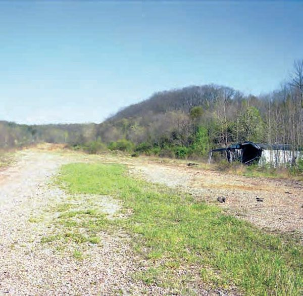 Part of a building still stands on the property, but just barely due to the years of abandonment. Although the property is in sad shape, this wide clearing offers another good view of the valley, which had an echoing roar that lasted from 1964 to 1976. (Photo Courtesy Bill Truby)