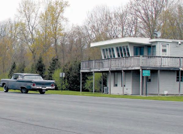 """Although it has been updated with a second-story deck and vinyl siding on the exterior, the timing tower still stands at the site of Connecticut Dragway. Signs that read """"Historical District"""" are placed in front of the tower, which is an indication that Consumers Union takes the historic property seriously. (Photo Courtesy Trent Sherrill)"""