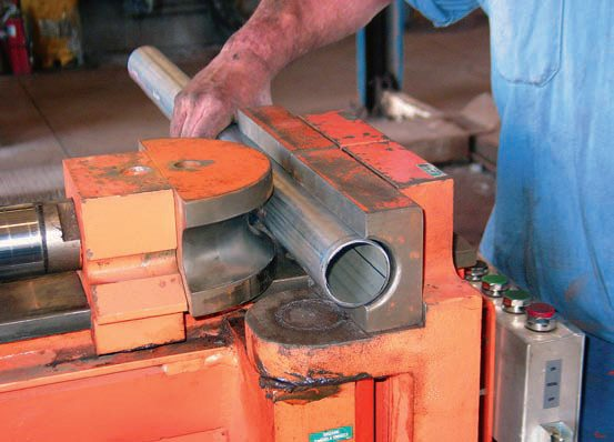 Using a crush-type bender machine, the pipe is placed between the radius die and a pair of backing shoes. The radius die generally features a 180-degree throat, while the backing shoes are straight