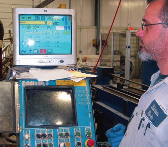 The exhaust pipe's design is programmed for the CNC bender. A CNC technician verifies that the correct program has been uploaded and monitors the bending process both at the dies and on the monitor screen.