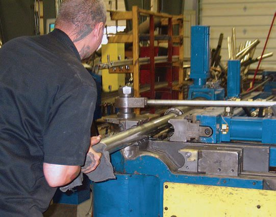Once the straight section of pipe is positioned in the CNC bender machine, the automated bender is set to run.