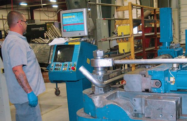 Header primary tube bending is accomplished on highly precise CNC mandrel-bending machines. Here, an Addison-McKee CNC pipe bender is programmed to run a specific engine-cylinder primary tube at Stainless Works.