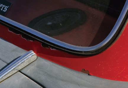 Another area where rust often forms is around window rubber, especially at the lower corners of rear windows. This, at first, appears to be the case on this '50 Ford, but a closer look shows that the custom 'flake paint on the roof is peeling because of poor prep and lack of sanding—which is also common around rubber window moldings.