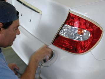 After a little protective taping, the crew started literally scuffing the car down with Scotchbrite pads as well as 1000-grit paper by hand and with a small orbital palm-sander.