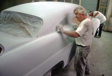 You can see that the rear window and side glass have been removed, with their custom moldings, but the headliner is still in place, so these areas had to be fully masked. Junior is carefully hand-sanding the side-window lip, especially in the tight corner where it meets the top.