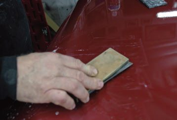 Most color sanding should be done with some sort of block. Bill cuts a semi-hard rubber squeegee slightly smaller than the folded paper, so he can hold the paper by the edges as he sands in back-and-forth strokes, starting with 1000 grit on this fairly rough paint.