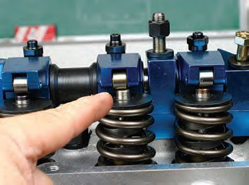 Adjusting shaft-mounted rockers (where a common full length shaft is featured) can be a time-consuming process in order to position each rocker's roller tip centered to each valve. Chances are you won't achieve alignment on the first try. To re-adjust, use a caliper to measure the required change, disassemble the shaft, reinstall the shims, and try again. It's not that difficult, but it takes patience.