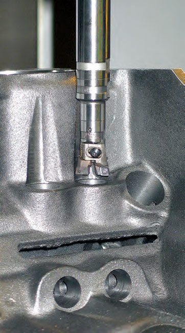 A CNC cutter spot faces lifter bore roofs in preparation of lifter bore centerline correction. With a programmed CNC machine, no indexing fixtures are needed for lifter bore correction.