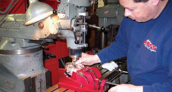 A dedicated precision piston vise allows the piston to be secured in the correct valve angle prior to pocket milling.