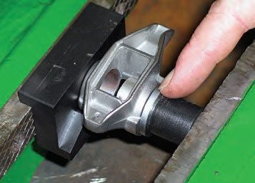 Using the Summit kit's mandrel, place the new bearing onto the mandrel and then the aluminum alignment sleeve. This aligns the new bearing with the rocker arm body. Push a new caged bearing into one side of the rocker.