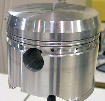 Once the piston program has been written, the machining process starts with skirt profiling, ring groove machining, and port drilling. Here the dome has been machined to a raw stage. With ring grooves machined relative to the pin bore and anticipated dome height, finish machining creates the final skirt profile, dome, and valve pockets. (Photo Courtesy Diamond Racing Products)